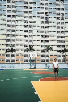 Mężczyzna stojący na boisku do koszykówki w pobliżu budynku