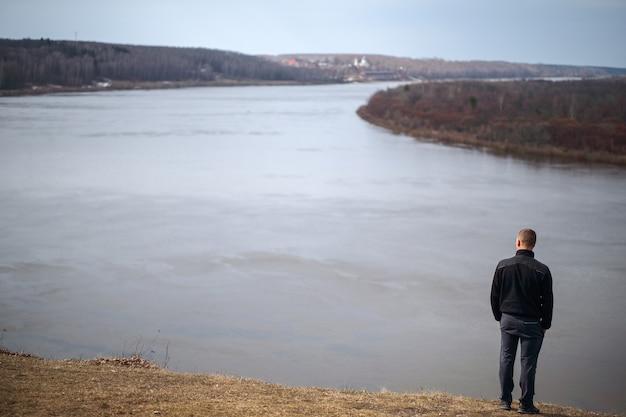 Mężczyzna stojący na brzegu rzeki i kontemplując