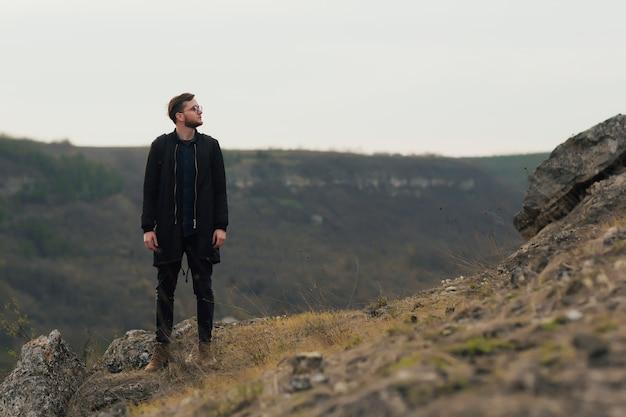 Mężczyzna stojący na górze i cieszący się widokiem natury