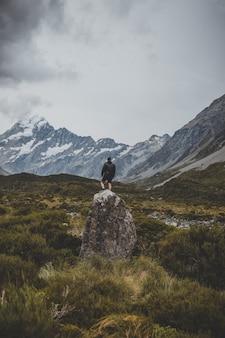 Mężczyzna stojący na kamieniu w hooker valley track z widokiem na mount cook w nowej zelandii
