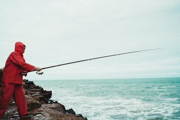 Mężczyzna stojący na skałach i połowów