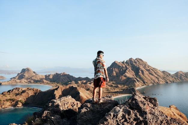 Mężczyzna stojący na szczycie skalnego wzgórza i podziwiający widok