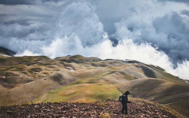 Mężczyzna stojący na wzgórzu pokrytym zielenią pod burzowym niebem w ciągu dnia