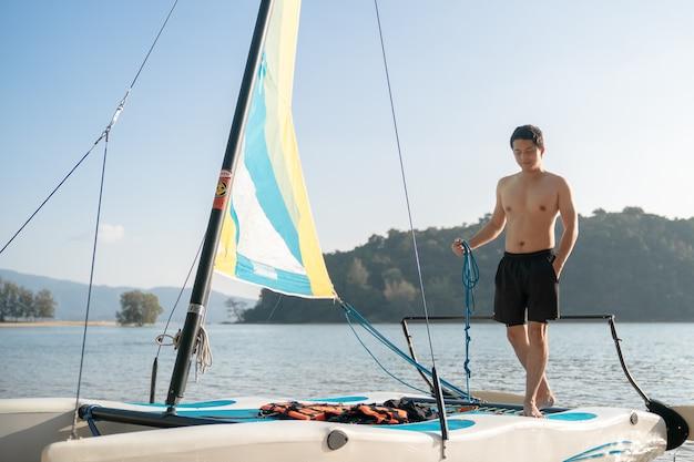 Mężczyzna stojący na żaglówkach. jacht żaglowy, regaty. styl życia sportów wodnych. lato.