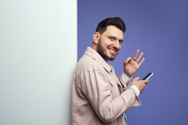 Mężczyzna stojący obok pustej białej ściany billboardowej i pokazujący ok gest