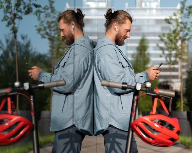 Mężczyzna stojący obok skutera podczas sprawdzania telefonu