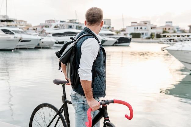 Mężczyzna stojący obok swojego roweru