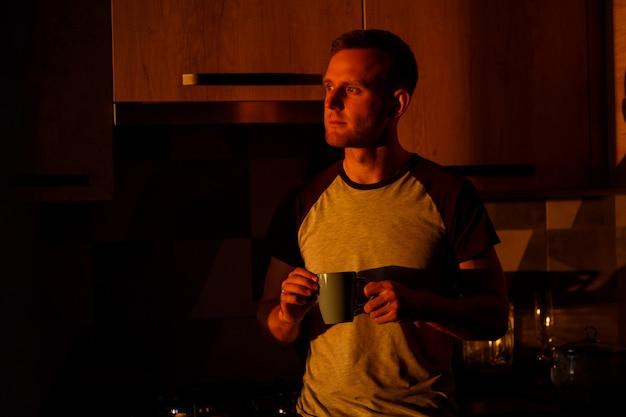 Mężczyzna stojący przed oknem w świetle zachodzącego słońca pije kawę w swojej kuchni