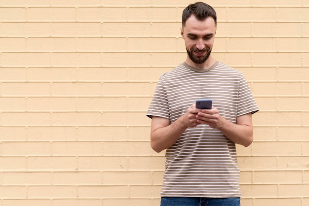 Mężczyzna stojący przed ścianą i korzystający z telefonu