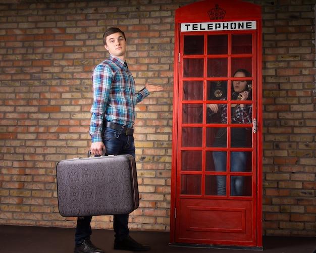 Mężczyzna stojący trzymający walizkę, wzruszający ramionami i gestykulujący, gdy jego żona dzwoni w czerwonej brytyjskiej budce telefonicznej