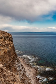 Mężczyzna stojący w pobliżu krawędzi urwiska z pięknym widokiem na morze