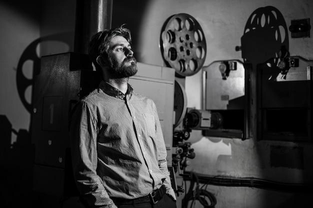 Mężczyzna stojący w pobliżu projektora filmowego w sali projekcyjnej