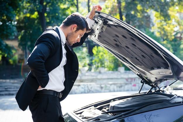 Mężczyzna stojący w pobliżu zepsutego samochodu z otwartym kapturem