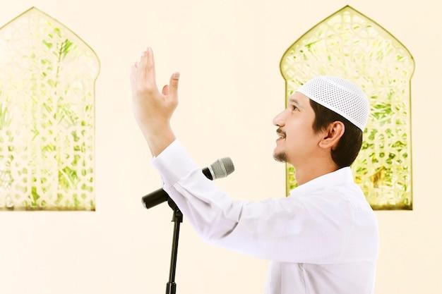 Mężczyzna stojący z podniesionymi rękami i wygłaszający kazanie na temat meczetu