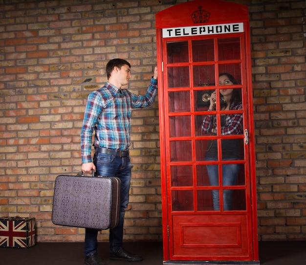 Mężczyzna stojący ze swoją walizką, próbujący przyciągnąć uwagę żony, gdy ta rozmawia z przyjaciółmi przez publiczny telefon w kultowej czerwonej brytyjskiej budce telefonicznej