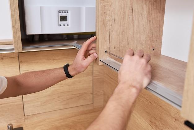 Mężczyzna stolarz instaluje półkę w szafce kuchennej