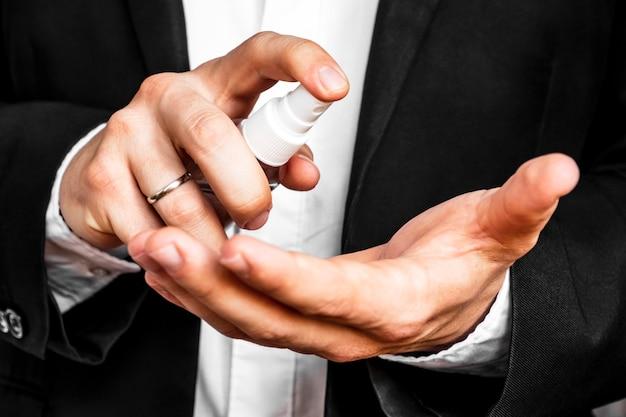 Mężczyzna stosując spray dezynfekujący na ręce