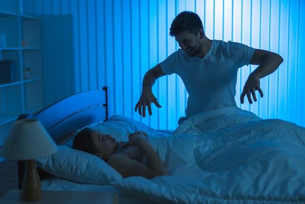 Mężczyzna straszy kobietę w łóżku. pora nocna