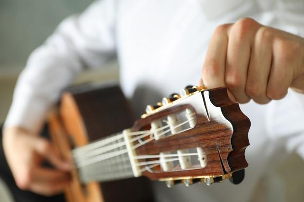 Mężczyzna stroi gitarę klasyczną