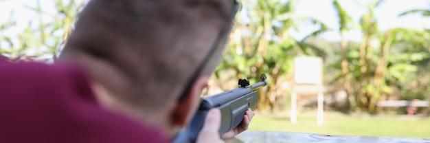 Mężczyzna strzela z broni do celu na strzelnicy ulicznej
