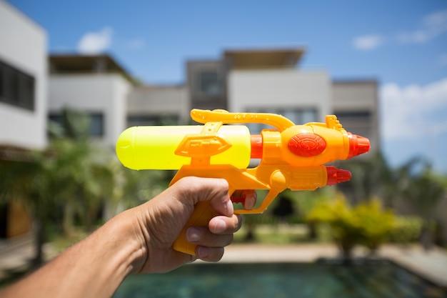 Mężczyzna strzela z pistoletu na wodę do kobiety, bawiąc się w basenie.