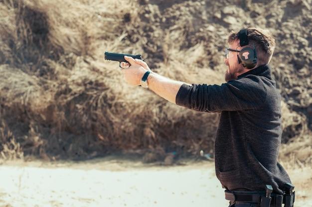 Mężczyzna strzelający z pistoletu podczas treningu z ochroną przed hałasem i okularami na tle kamiennej ściany