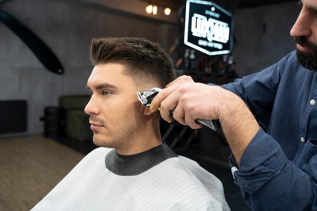 Mężczyzna strzyżący fryzurę w salonie w średnim ujęciu
