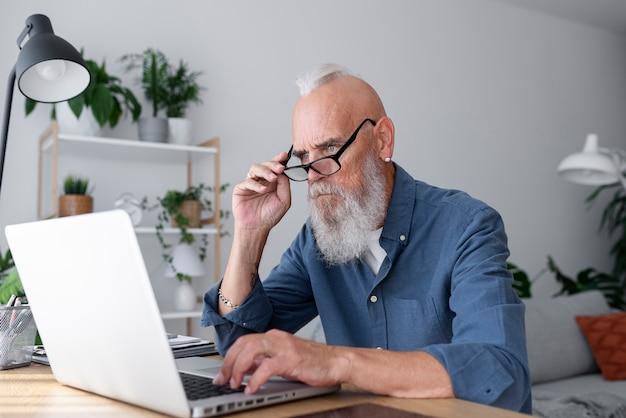 Mężczyzna studiujący z laptopem w średnim ujęciu