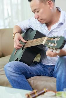 Mężczyzna studiuje grać na gitarze