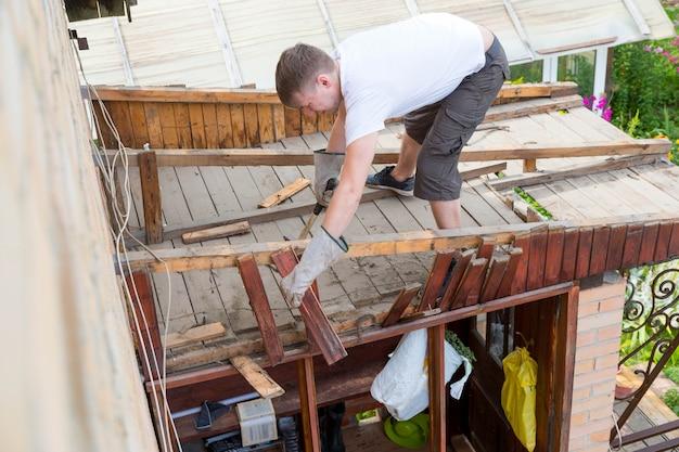 Mężczyzna stuka starą, zgniłą drewnianą deskę młotkiem z parsowania dachu