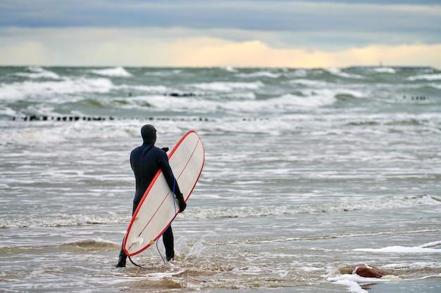 Mężczyzna surfer w czarnym stroju kąpielowym idący wzdłuż morza i trzymając w ręku białą deskę surfingową. ciepły dzień, piękne zachmurzone niebo, scena natury