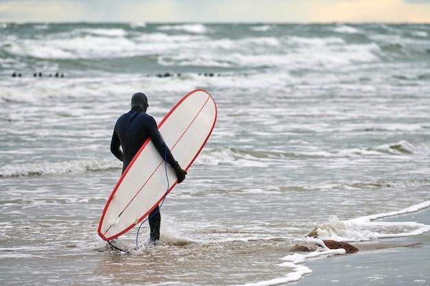Mężczyzna surfer w czarnym stroju kąpielowym idący wzdłuż morza i trzymając w ręku białą deskę surfingową