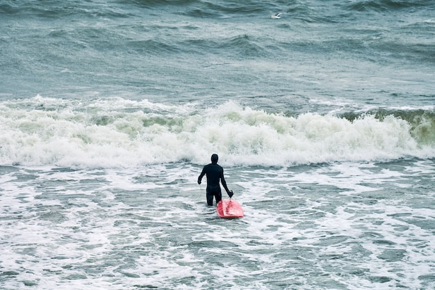 Mężczyzna surfer w czarnym stroju kąpielowym w morzu z czerwoną deską surfingową czeka na wielką falę.