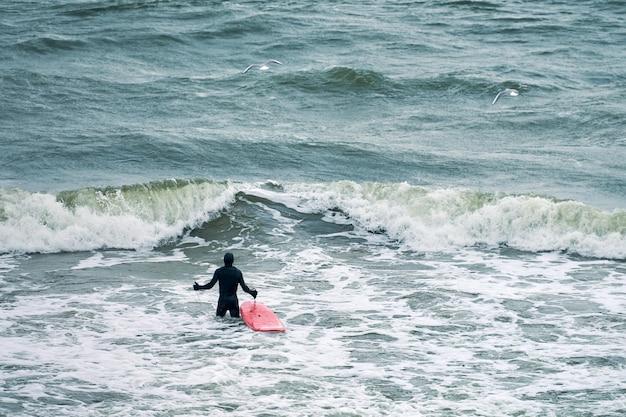 Mężczyzna surfer w czarnym stroju kąpielowym w oceanie z czerwoną deską surfingową czeka na wielką falę