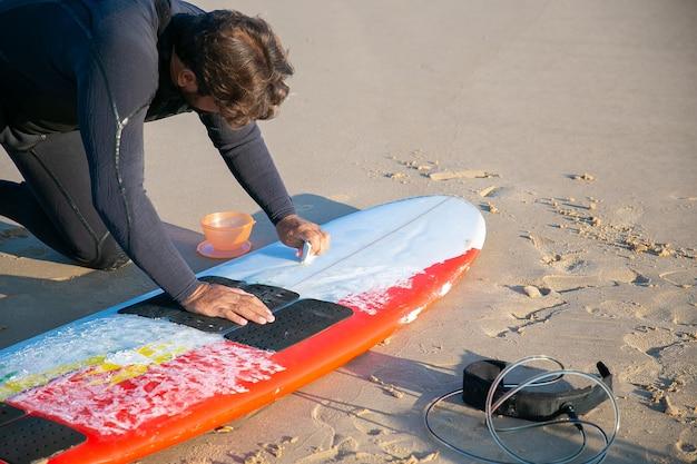 Mężczyzna surfer w kombinezonie do polerowania deski surfingowej z woskiem na piasku