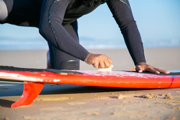 Mężczyzna surfer w kombinezonie woskującym deskę surfingową na piasku na plaży oceanu