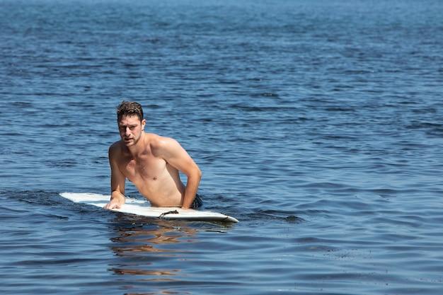 Mężczyzna surfujący samotnie w oceanie z kopią miejsca