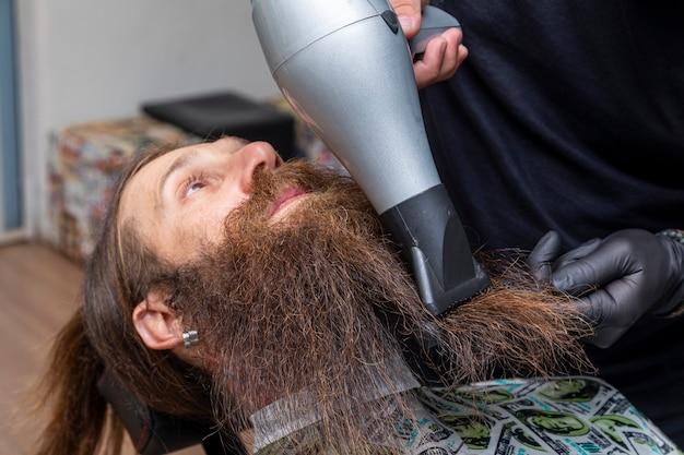 Mężczyzna suszy brodę u fryzjera.