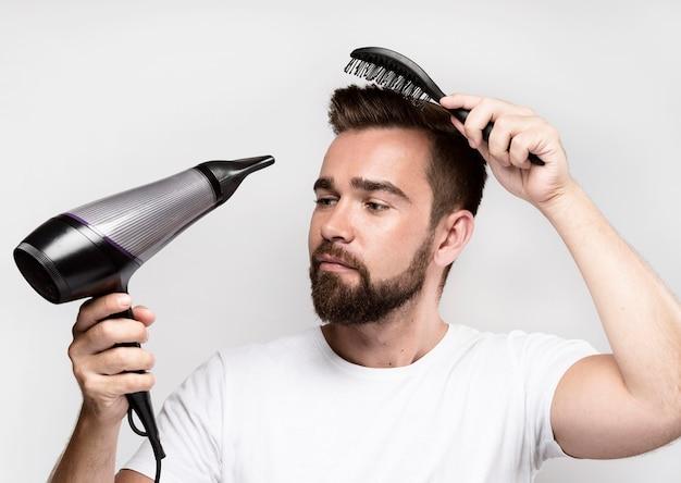 Mężczyzna suszy włosy i je szczotkuje