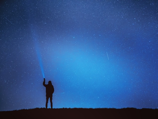 Mężczyzna świeci latarnię na niebie