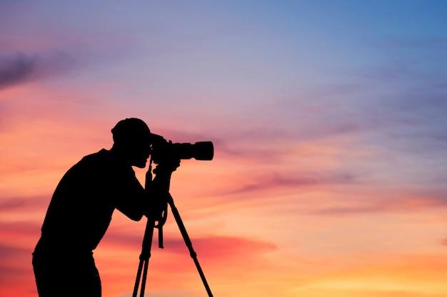 Mężczyzna sylwetka fotografa zrobić zdjęcie na wzgórzu wysokiej góry profesjonalny aparat fotografowania strzelanie krajobraz zachód słońca na szczycie góry natura zmierzch niebo
