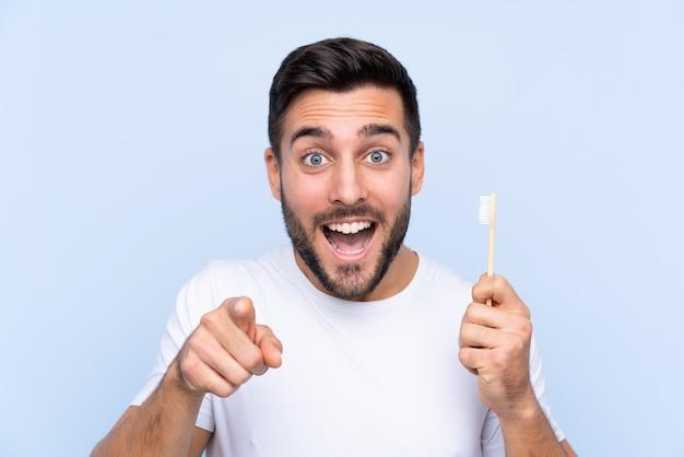 Mężczyzna szczotkuje jego zęby nad odosobnioną ścianą z brodą