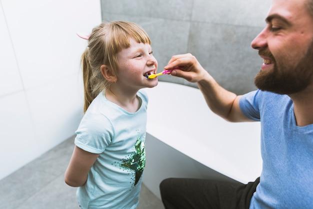 Mężczyzna szczotkuje zęby córka