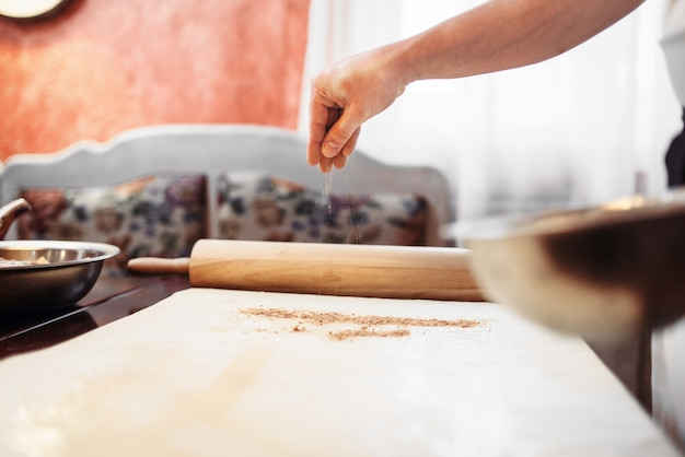 Mężczyzna szef kuchni przekazać ciasto, gotowanie strudla jabłkowego. domowy słodki deser, proces przygotowania ciasta