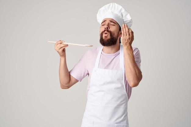 Mężczyzna szef kuchni w fartuchu chodzącym profesjonalnej restauracji kulinarnej