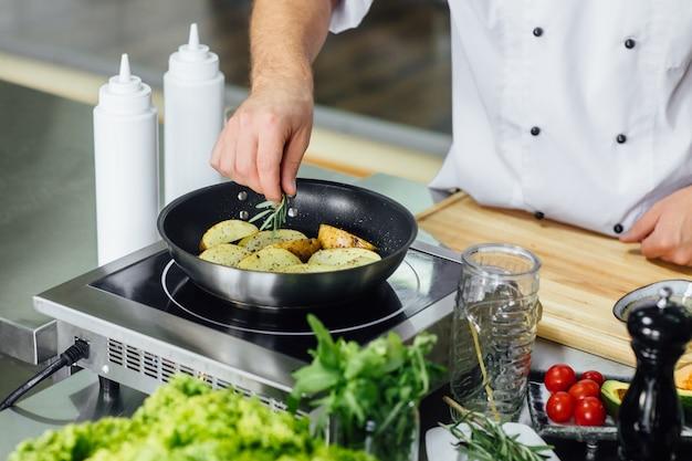 Mężczyzna szefa kuchni gotuje sos ze świeżych ziemniaków w kuchni restauracji?