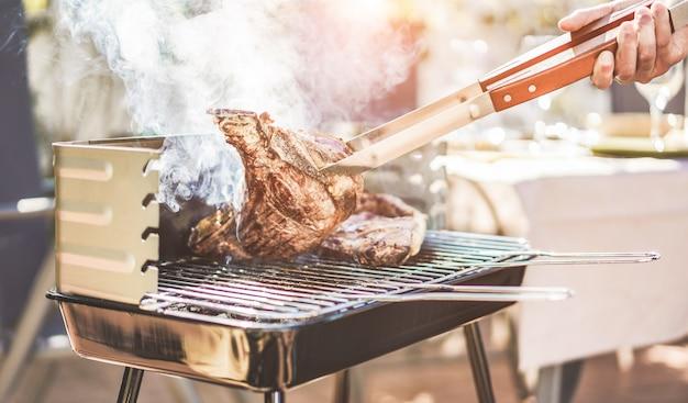 Mężczyzna szefa kuchni grill stek t-bone na kolację z grilla na świeżym powietrzu - człowiek gotowania mięsa na rodzinny posiłek grill na zewnątrz w ogrodzie przydomowym
