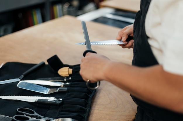 Mężczyzna szefa kuchni ostrzy noże