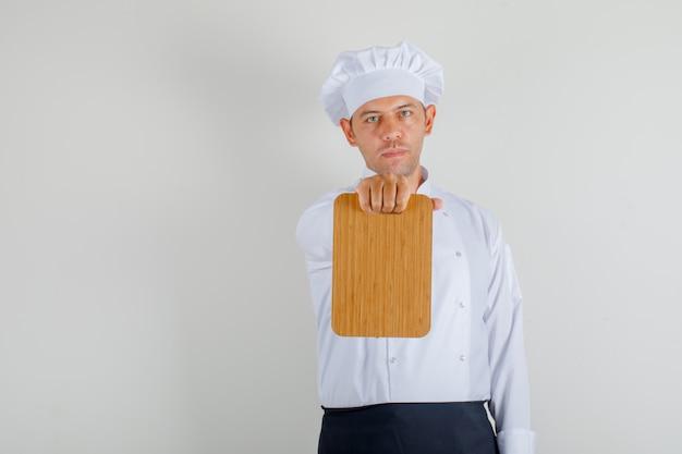 Mężczyzna szefa kuchni pokazano deskę do krojenia w mundurze, fartuch i kapelusz