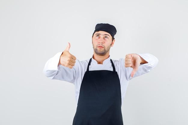 Mężczyzna szefa kuchni pokazujący kciuki w dół iw górę w mundurze, fartuchu i zamyślony. przedni widok.